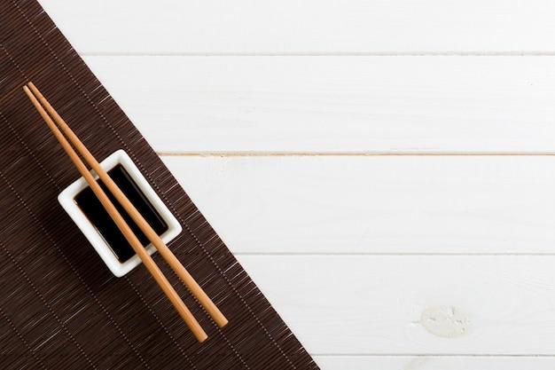 Estera de bambú y salsa de soja con palillos de sushi en mesa de madera blanca.