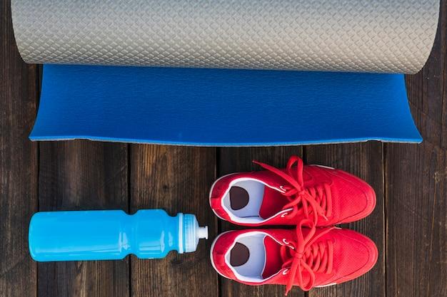 Estera enrollada para ejercicios con botella de agua y zapatos deportivos en mesa de madera