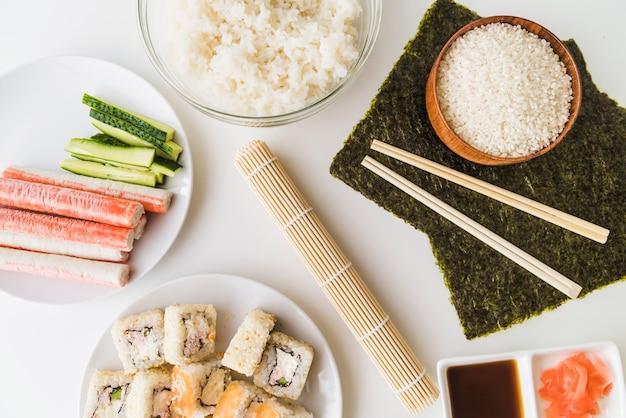 Estera de sushi rodeada de ingredientes