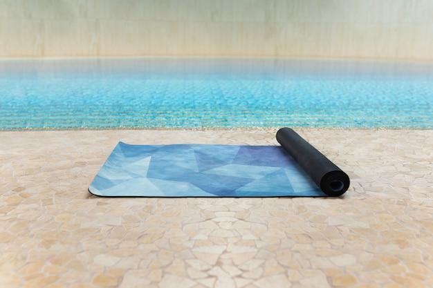 Estera de yoga azul en el interior del gimnasio después de una clase de yoga en el piso cerca de una piscina, de cerca