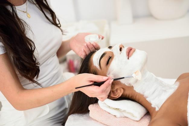 Estética aplicando una máscara a la cara de una mujer hermosa.