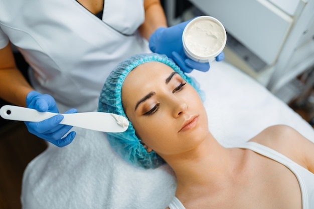 Esteticista aplica la crema a la cara de la paciente, preparación de botox. procedimiento de rejuvenecimiento en salón de esteticista. médico y mujer, cirugía estética contra arrugas y envejecimiento