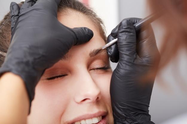 Esteticista aplica maquillaje permanente en las cejas