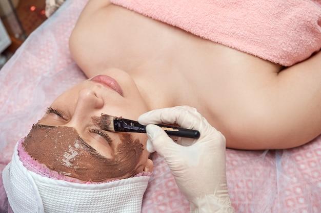 Esteticista aplica una mascarilla nutritiva en el rostro con un cepillo.