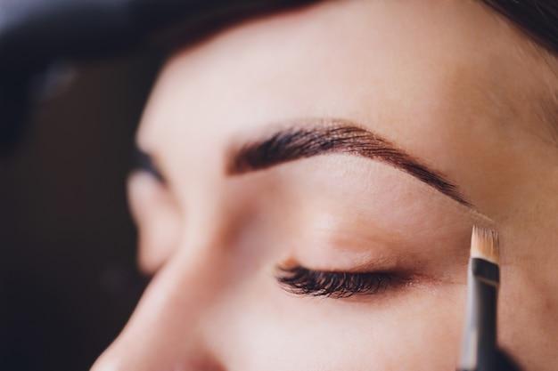 Esteticista aplica pintura de henna en cejas recortadas en un salón de belleza