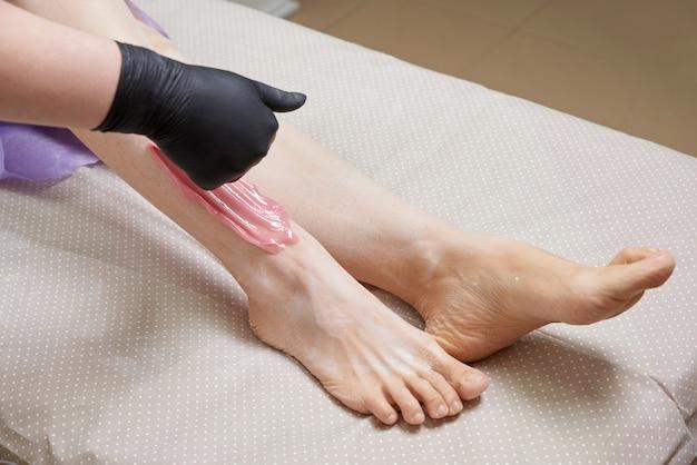 Esteticista aplicando cera en la pierna femenina en el salón de belleza spa