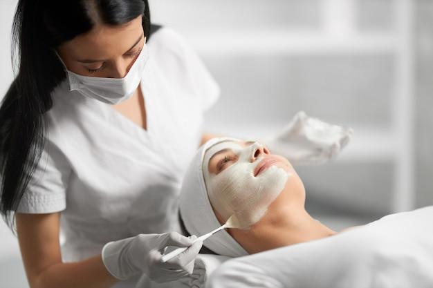 Esteticista aplicando crema blanca especial para el paciente