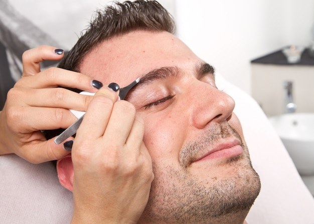 Esteticista arrancando las cejas de un hombre hermoso con unas pinzas en un salón de belleza