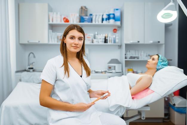 Esteticista cerca del paciente en la mesa de tratamiento, preparación de la inyección de botox. procedimiento de rejuvenecimiento en salón de esteticista. médico y mujer, cirugía estética contra arrugas y envejecimiento