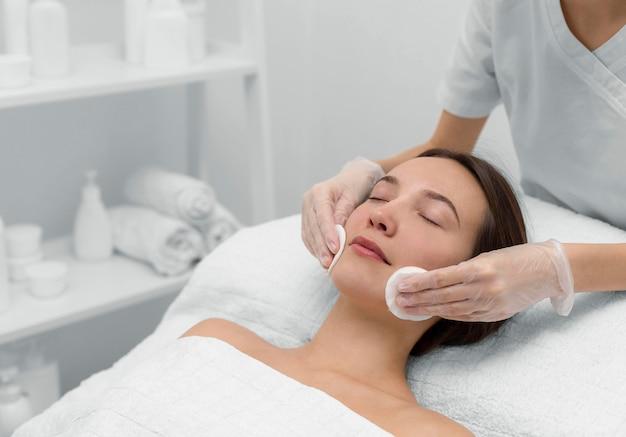 Esteticista con clienta en el salón de rutina de cuidado facial