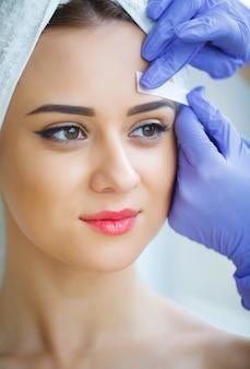 Esteticista depilando las cejas de la mujer joven en el centro de spa