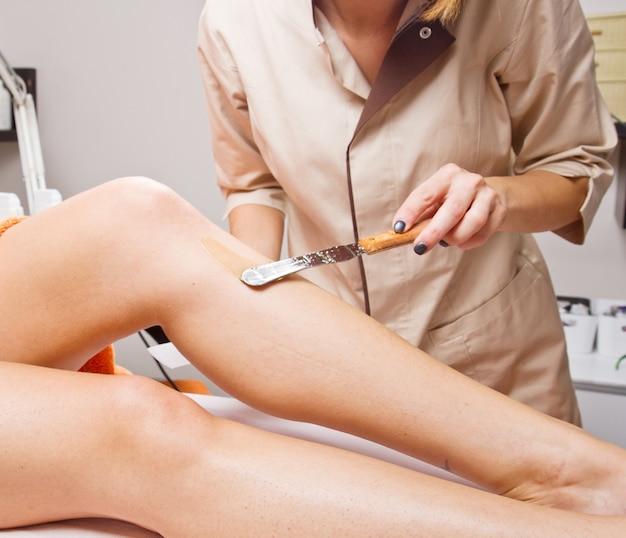 Esteticista depilando la pierna de una mujer aplicando una tira de material sobre la cera caliente para eliminar el vello