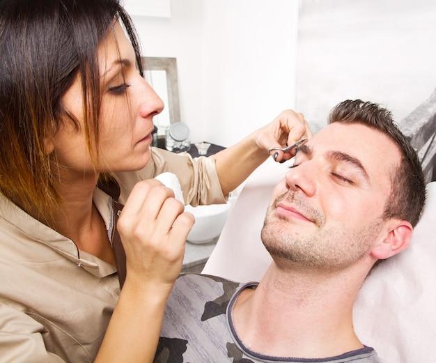 Esteticista depilarse las cejas de un hombre hermoso con pinzas en un salón de belleza