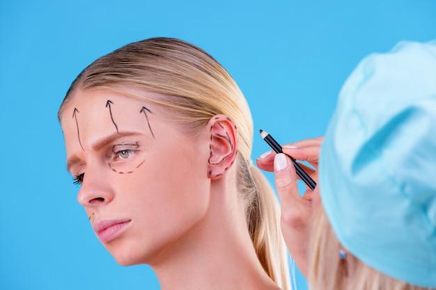 Esteticista dibujar líneas de corrección en la cara de mujer. antes de la operación de cirugía plástica. aislado en azul