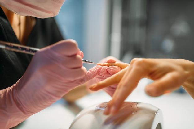 Esteticista en guantes de color rosa pega las uñas de la clienta, manicura en salón de belleza. manicurista haciendo procedimiento cosmético de cuidado de manos