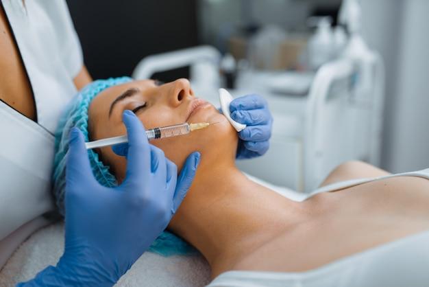 Esteticista en guantes da inyección de botox en la barbilla a una paciente en la mesa de tratamiento. procedimiento de rejuvenecimiento en salón de esteticista. médico con jeringa y mujer, cirugía estética contra las arrugas