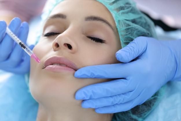 Esteticista en guantes de goma hace inyección de colágeno en labios de mujer joven