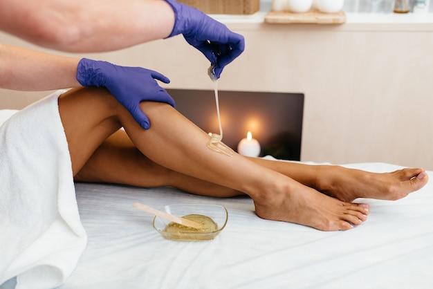 Esteticista en guantes de látex negro aplica pasta de azúcar para eliminar el vello en las piernas del paciente /