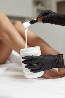 Esteticista hace depilación de mujer joven en su pierna con cera
