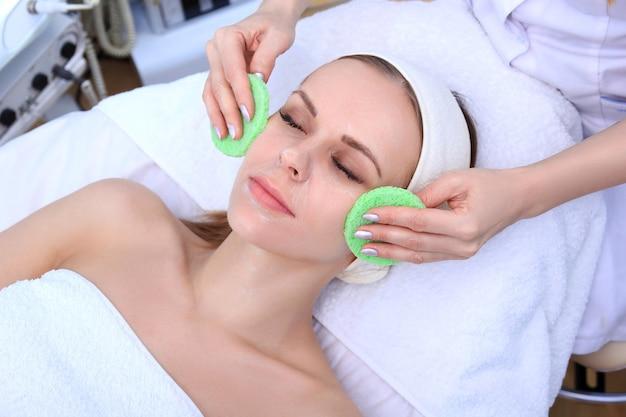Esteticista hace facial de limpieza y exfoliación para una chica hermosa. salón de belleza.