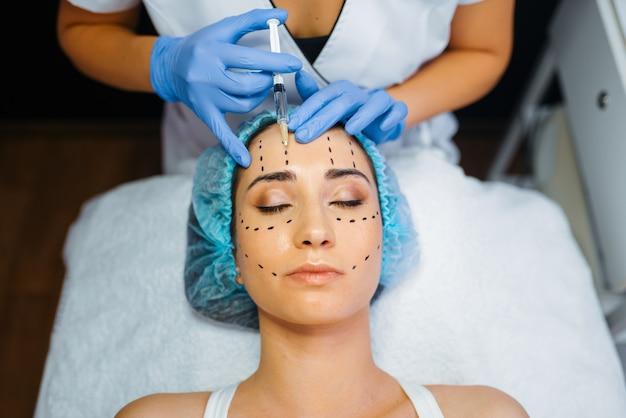 Esteticista hace inyección de botox en líneas punteadas en la cara del paciente femenino, preparación de inyecciones de botox. procedimiento de rejuvenecimiento en salón de esteticista. cirugía estética contra arrugas y envejecimiento