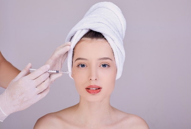 Esteticista hace la inyección facial a una joven morena.
