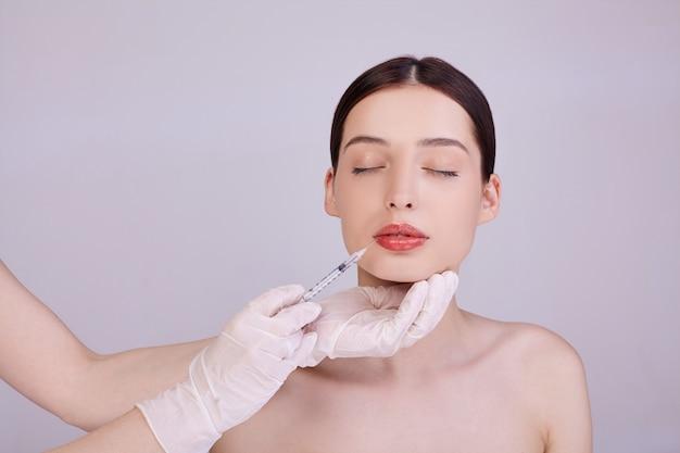 Esteticista hace una inyección en los labios de una mujer.