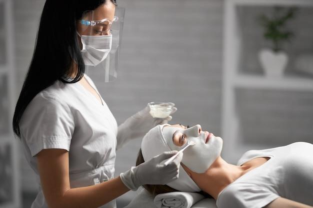 Esteticista haciendo limpieza facial con cosméticos para el paciente.