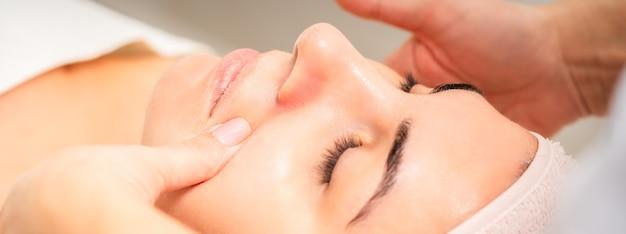 Esteticista haciendo masaje facial de drenaje linfático o masaje de lifting facial en el salón de belleza.