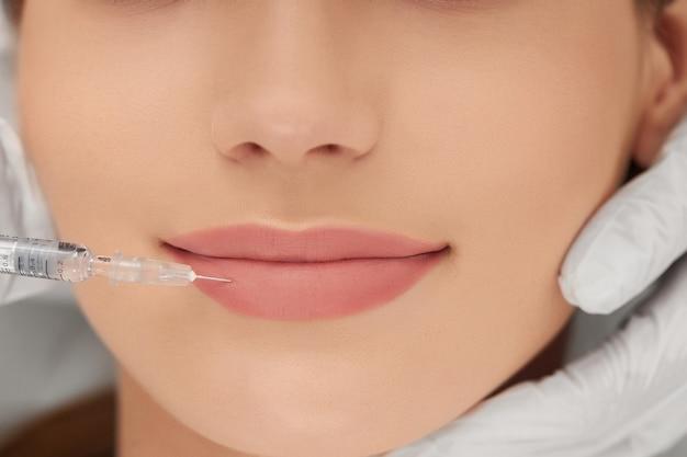Esteticista haciendo procedimiento para aumento de labios.