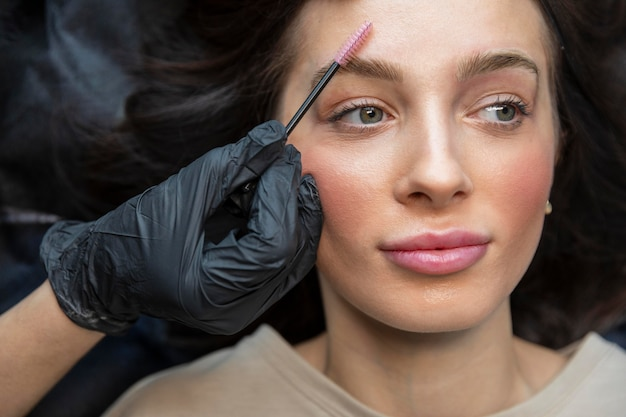 Esteticista haciendo un tratamiento de cejas para su cliente.