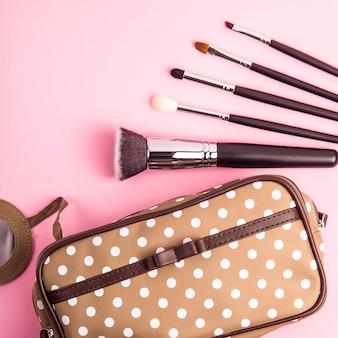 Esteticista de lunares marrones con pinceles de maquillaje sobre un fondo rosa brillante. estilo retro. vista superior, plano