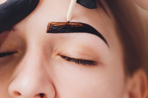 Esteticista: el maquillador aplica henna de pintura en cejas previamente depiladas, de diseño y recortadas en un salón de belleza en la corrección de la sesión. cuidado profesional para la cara.