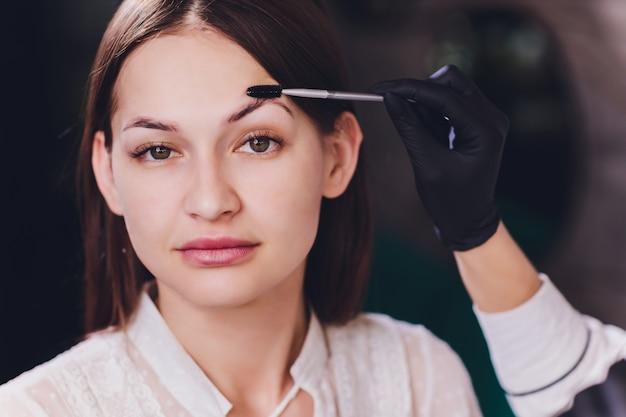 Esteticista-maquilladora aplica henna de pintura en cejas previamente depiladas, de diseño y recortadas en un salón de belleza en la corrección de la sesión. cuidado profesional para la cara.