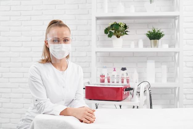 Esteticista en máscara protectora esperando clientes