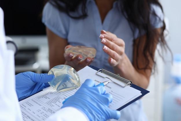 Esteticista médico llena el contrato y los deseos del paciente