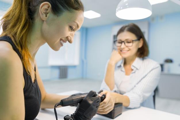 Esteticista de mujer en salón de belleza haciendo manicura