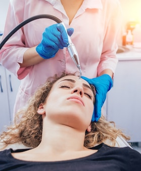 Esteticista y el paciente en la clínica de medicina estética que reciben un tratamiento.