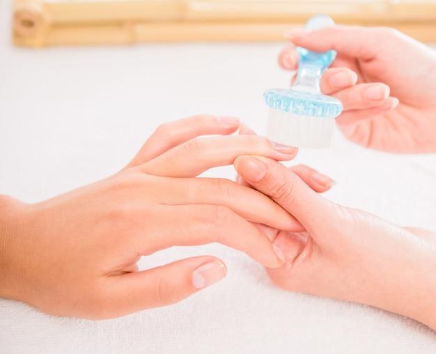 Esteticista uñas con pincel a su cliente en salón de belleza.