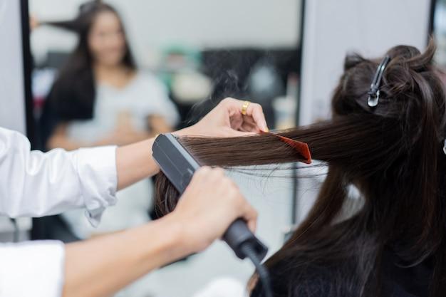 Esteticista planchar clientes de cabello
