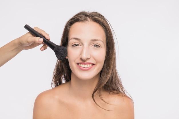 Esteticista poniendo polvo en mujer sonriente