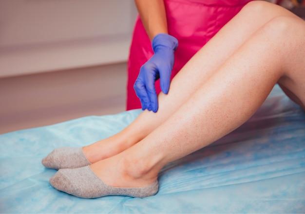 La esteticista se prepara para la depilación y aplica la crema.