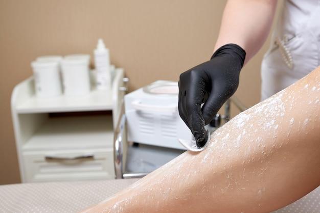 Esteticista preparándose para depilar las piernas femeninas en el centro de spa. preparación para la depilación, poniendo un poco de polvo blanco.