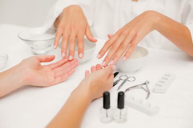 Esteticista presentación clientes mujeres uñas en el salón de belleza del spa