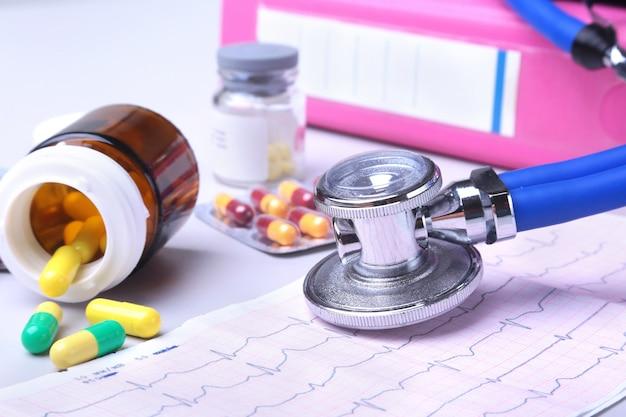 Estetoscopio acostado con receta rx con pastillas surtidas. vida sana o concepto de seguro.