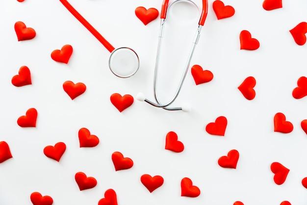 Estetoscopio aislado en blanco simple visto desde arriba rodeado de corazones rojos.