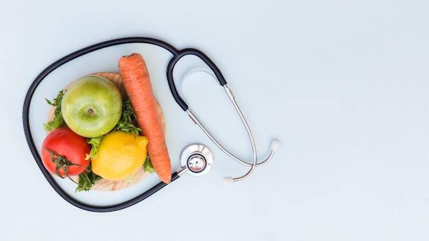 Estetoscopio alrededor de las verduras y frutas frescas sobre fondo blanco