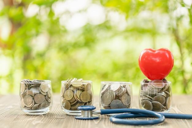 Estetoscopio azul y tarro de monedas en la mesa de madera. concepto de cheques financieros y de dinero