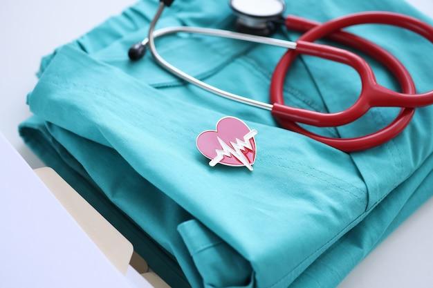 Estetoscopio azul traje médico y signo de cardiograma en la mesa