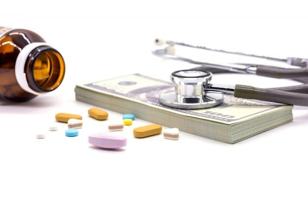 Estetoscopio con banco de dólar y cápsulas de medicina